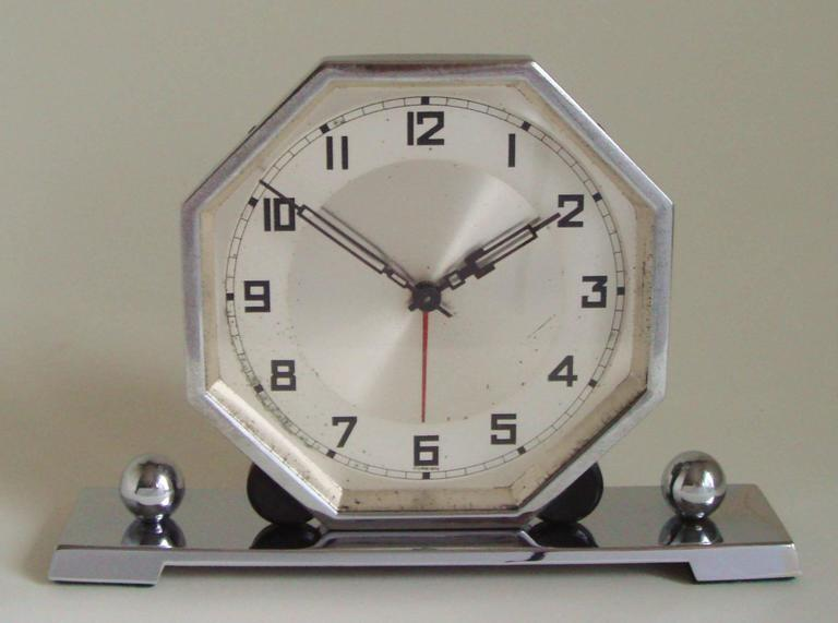 The hexagonal chrome body and bezel of this German Art Deco alarm clock stands on an oblong chrome footed plinth and is held in place by two demi-lunes of black Bakelite and bookended by two chrome spheres. The face does have some age spots but the