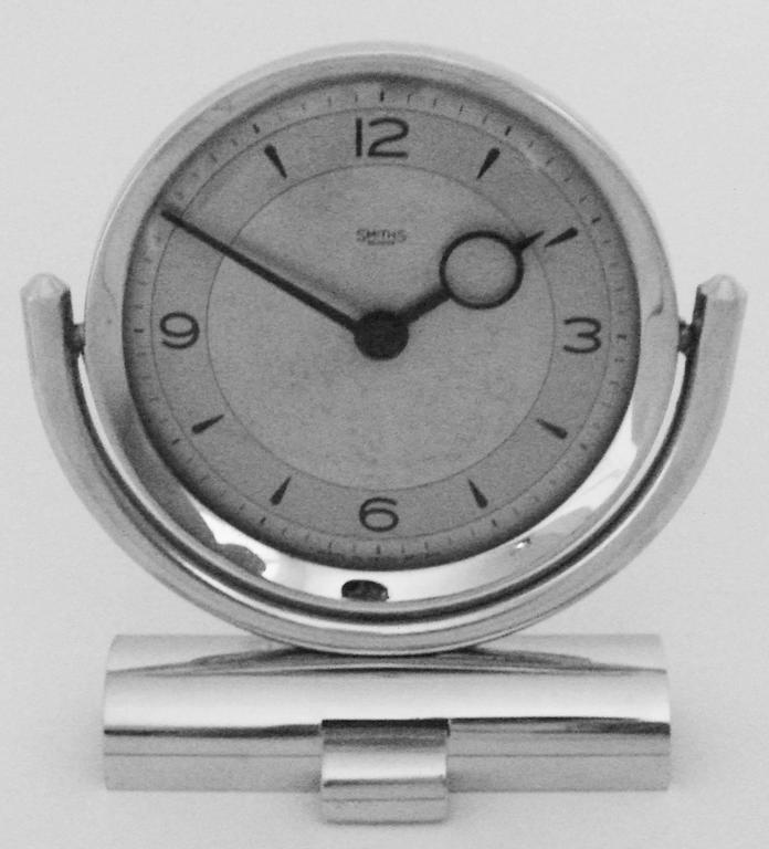 This eccentrically designed English Mid-Century Modern chrome desk clock has a 30-hour mechanical movement. It tilts backwards and forwards on a horizontal chrome arc and is supported on a base that is almost Art Deco in design. Both the original