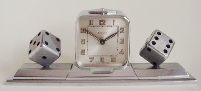 This beautifully engineered French Art Deco desk set features a chrome-plated brass Bayard mechanical alarm clock mounted on a heavy chrome plated bronze base. This clock is flanked on either side by a detachable plated bronze paperweight each with