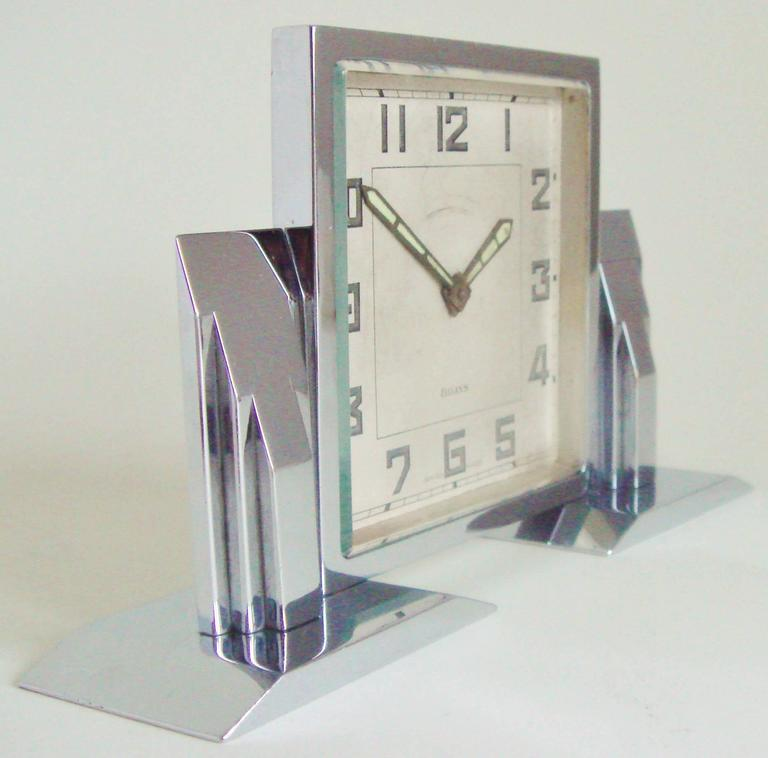 This is a beautiful and architecturally designed small Swiss Art Deco mechanical eight-day desk clock. It has its original chrome plate to both the front and back which is near perfect condition. The face shows only light age and there is a slight