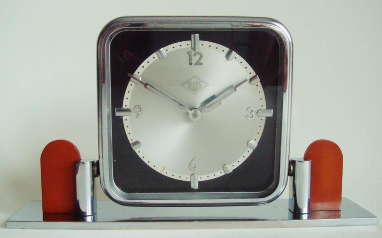 This German Art Deco tilting chrome and bakelite mechanical table clock was a presentation piece from the German heavy goods and engineering company of Orenstein & Koppel and bears their inter-war logo to the face. In 1935 as part of Hitler's