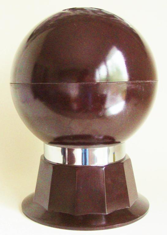 This American Mid-Century brown bakelite and chrome bar set takes the form of a life-size bowling ball standing on a twelve sided fluted plinth that is bound in chrome. When the hemisphere lid of the ball is lifted off, by using the three finger
