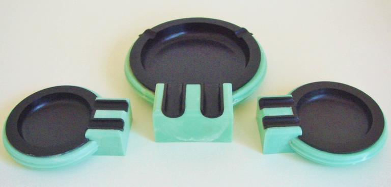 This set of British Art Deco black Bakelite and aqua phenolic ashtrays represent the third version of an iconic design that was originally produced for the launch of the Cunard Liner, RMS Queen Mary. The first or