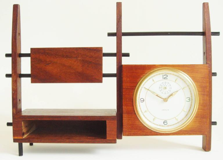 This beautifully executed Italian Mid-Century Modern Veglia mechanical alarm clock takes the form of a miniature wall unit and its design plays off the contrasting surfaces of teak and rosewood. Three tapering vertical posts support a rosewood