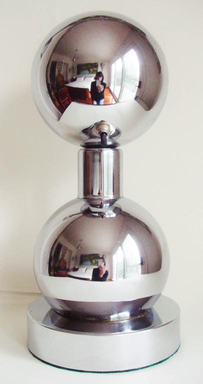 This unusual American space age, double-sphere chrome lamp with its eyeball shade is designed to sit on a table facing the wall in order to throw light on a picture or wall hanging. This style of picture light is hard to find and this particular one