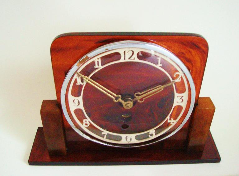 This stylish German Art Deco, key-wind, mechanical mantel clock features a body of translucent tortoiseshell Lucite. This is supported by blocks of opaque tortoise shell Bakelite and mounted to an oblong base of translucent tortoiseshell Lucite.