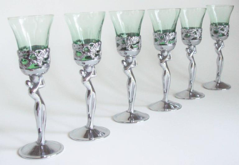 This stylish set of six Japanese Art Deco chrome liqueur cups each feature a stylized androgynous nude figure holding a removable pale green glass. They were made for export to the West and show the unusual combination of a Hagenaur like figure with