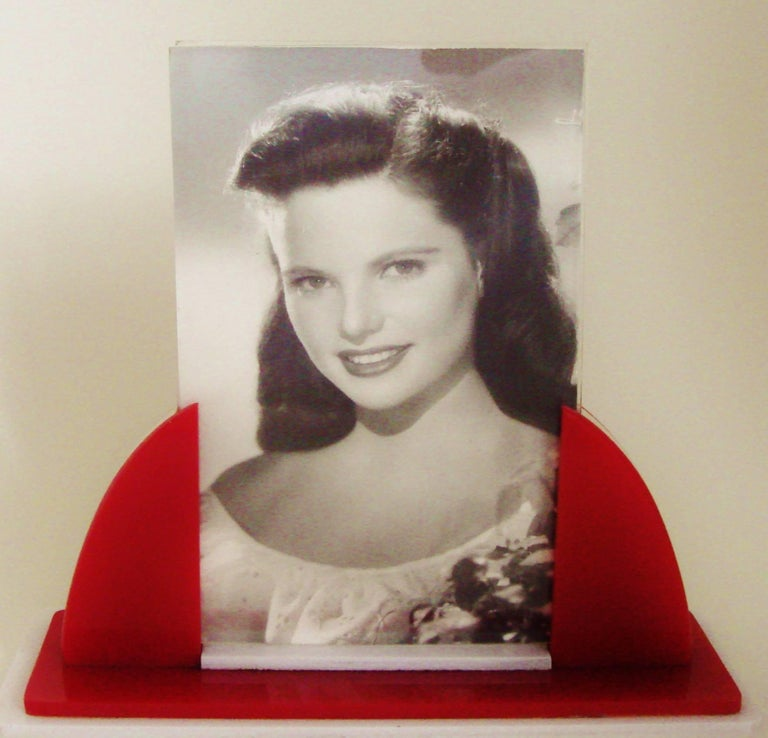 This English Art Deco photo frame features an Odeon style arrangement of layers of red and white Lucite. The photo itself (3.25 in X 5 in) is sandwiched between a thin front sheet of clear Lucite and a thick backing sheet of clear Lucite. The frame