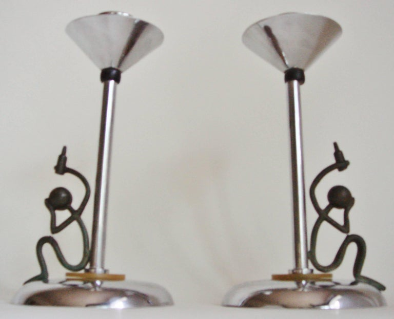 This fun and rare pare of English Art Deco chrome-plated candlesticks are both accented with a green/yellow marbled Bakelite disk at the base and black Bakelite spheres beneath each conical bobeche. Seated on each base and leaning on the chrome