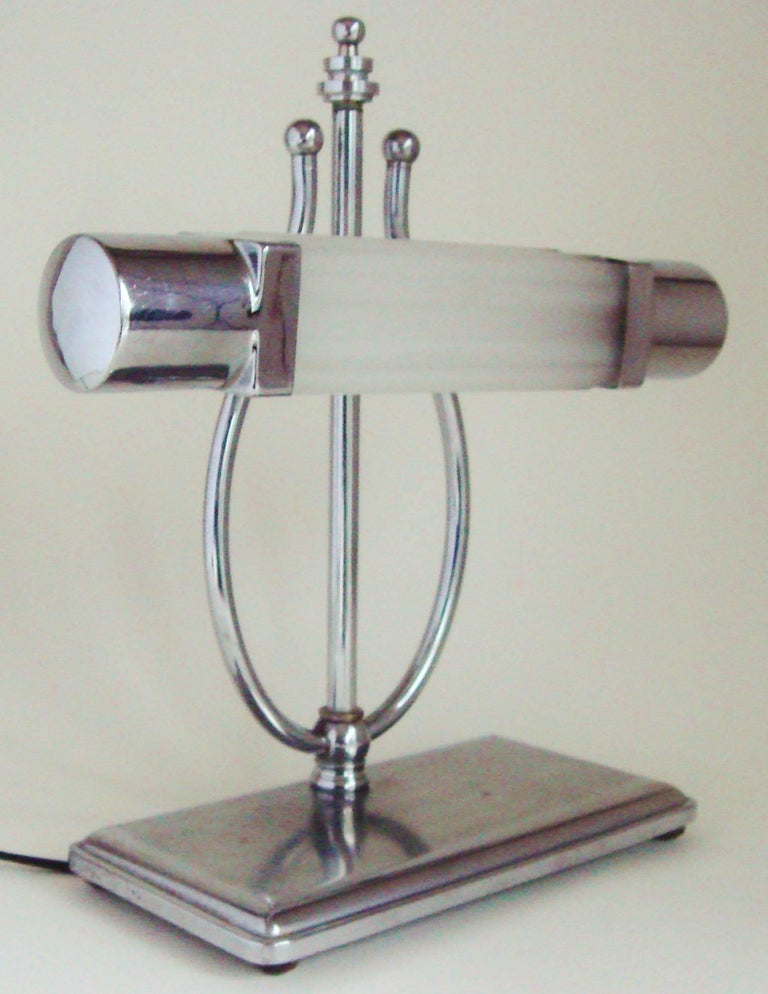 This American Art Deco piano lamp features a ribbed rectangular frosted glass shade with chrome caps at either end. This is affixed to a lyre shaped support that rises from a rectangular shaped, polished and brushed chrome base standing on four bun