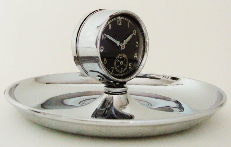 This unusual German Art Deco chrome cigar ashtray features a circular chrome dish with a black-faced 2.13 in diameter mechanical clock mounted to the center. This piece displays beautifully with the dish in excellent condition and the clock itself