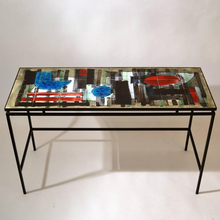 Modernist desk or console table with hand-painted tiled top in abstract design with splashes of bright colors red and blue on a suspended black metal frame, signed by Juliette Belarti, Belgium, circa 1960.