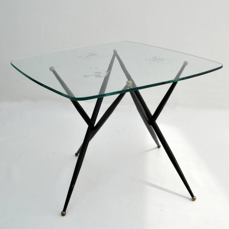 Game or coffee table expressing entertainment in theater, music and card games. The top shows three groups of pictograms etched in the clear glass in a typical 1950's style. The sculptural V-shaped tapered black metal legs are finished by brass