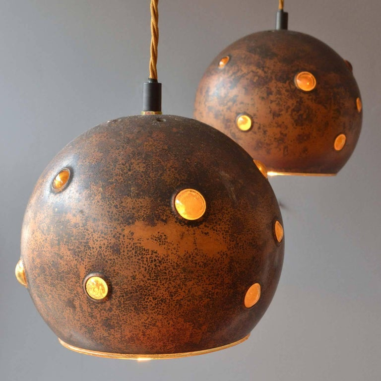 Each of these lamps is unique in its execution. Yellow glass creates bubbles by being blown into an oxidised copper spherical shell. The lamps can be adjusted to alternating heights. They are rewired with antique gold braided flex. Designed by the