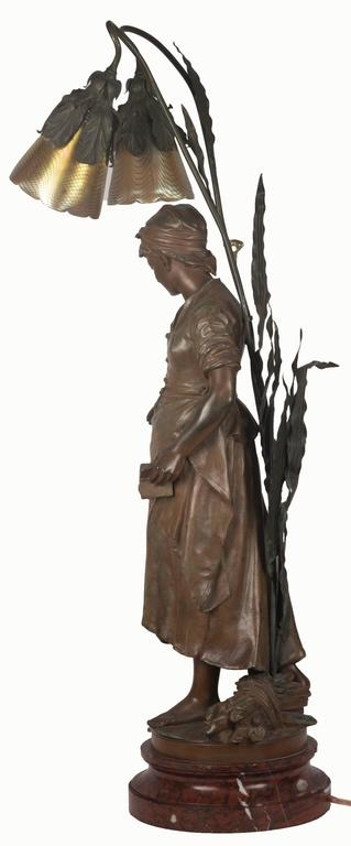 A finely detailed depiction of a female peasant dressed in simple garments, head wrap and apron, holding a small book in one hand while reaching out with the other. A small bushel of sticks sits at her bare feet. The original spelter figure, signed
