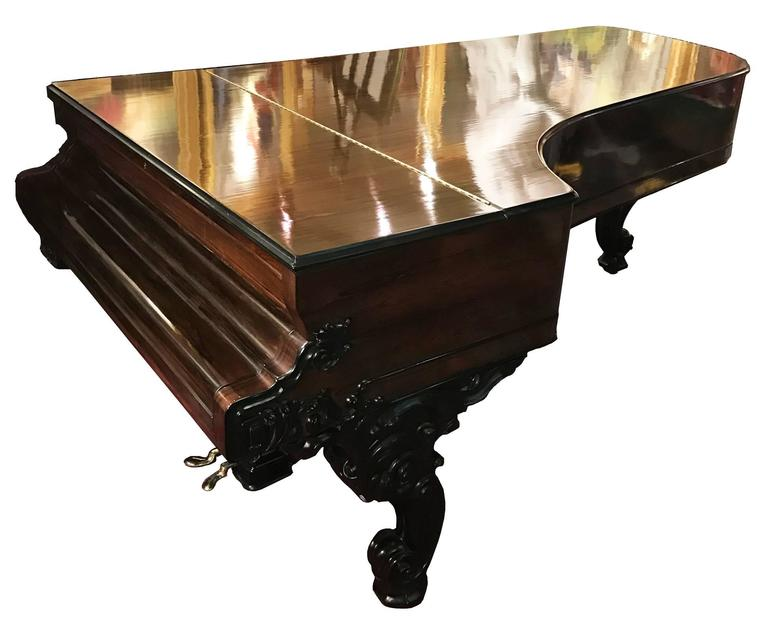 A lovely, fully restored 1866 Steinway & Sons concert grand piano with rosewood case. The elegantly carved Rococo-style scrolled legs and ornate foliate details are ebonized, producing a striking contrast against the case, while the pierced and