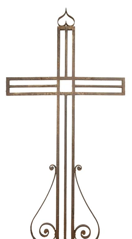 A late 19th century crucifix constructed in wrought iron in a simple geometric form, embedded in a stone pedestal.