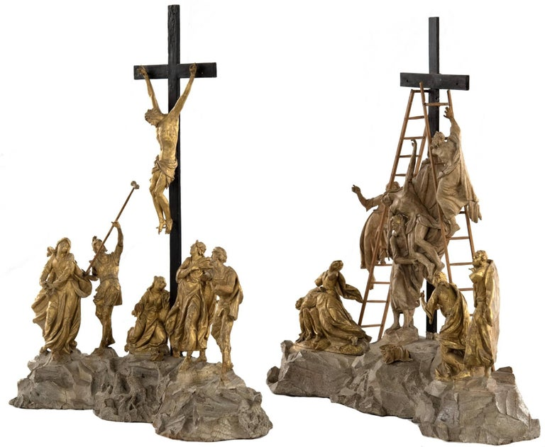 A set of finely hand-carved wooden figural scenes, decorated with gold leaf, depicting two integral events of the crucifixion of Christ. In each composition, figural groupings surround the cross that is mounted into the naturalized rocky ground; the