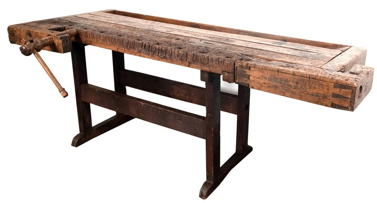 The form of this 150-year-old walnut bench is much older; and can be found in descriptions dating to the early middle ages. The product of successive generations of improved forms, the table is a kind of all-purpose surface, with clamps, holders,