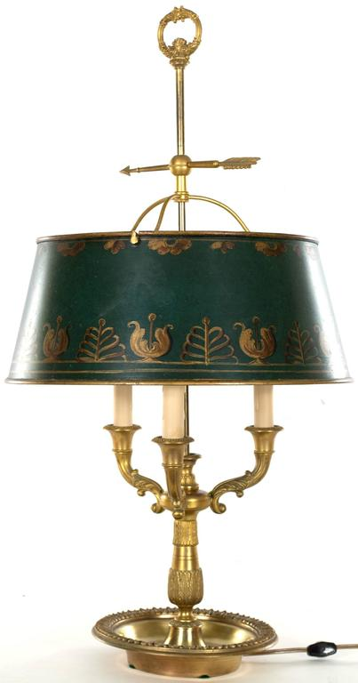 A charming table lamp in the form of a three-armed candelabra, with a green painted and gilt metal shade, made in England during the third quarter of the nineteenth century.