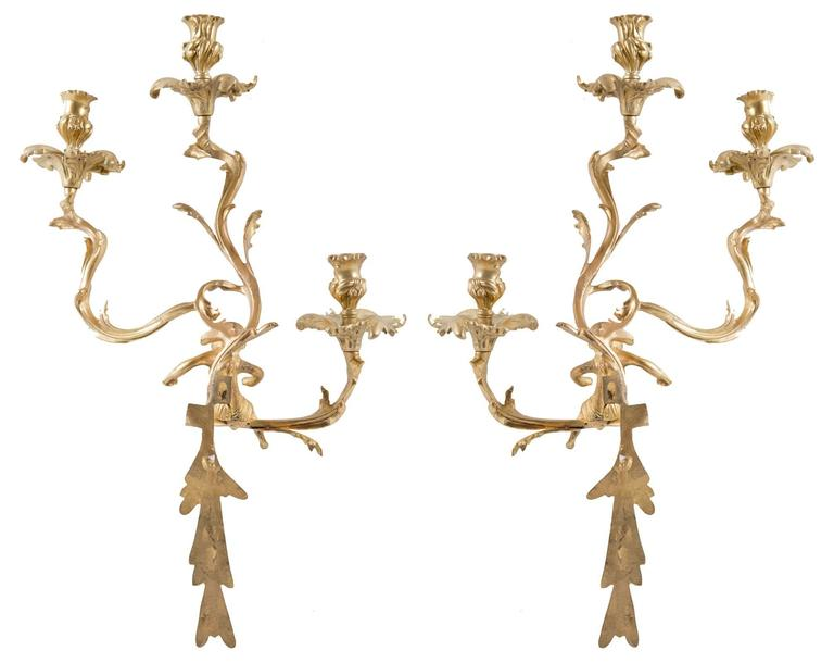 A pair of Louis XV-style gilt wall sconces with three scrolling foliate arms supporting thistle-form sockets, with chased hanging tendrils, and mounted with the figure of a centaur.