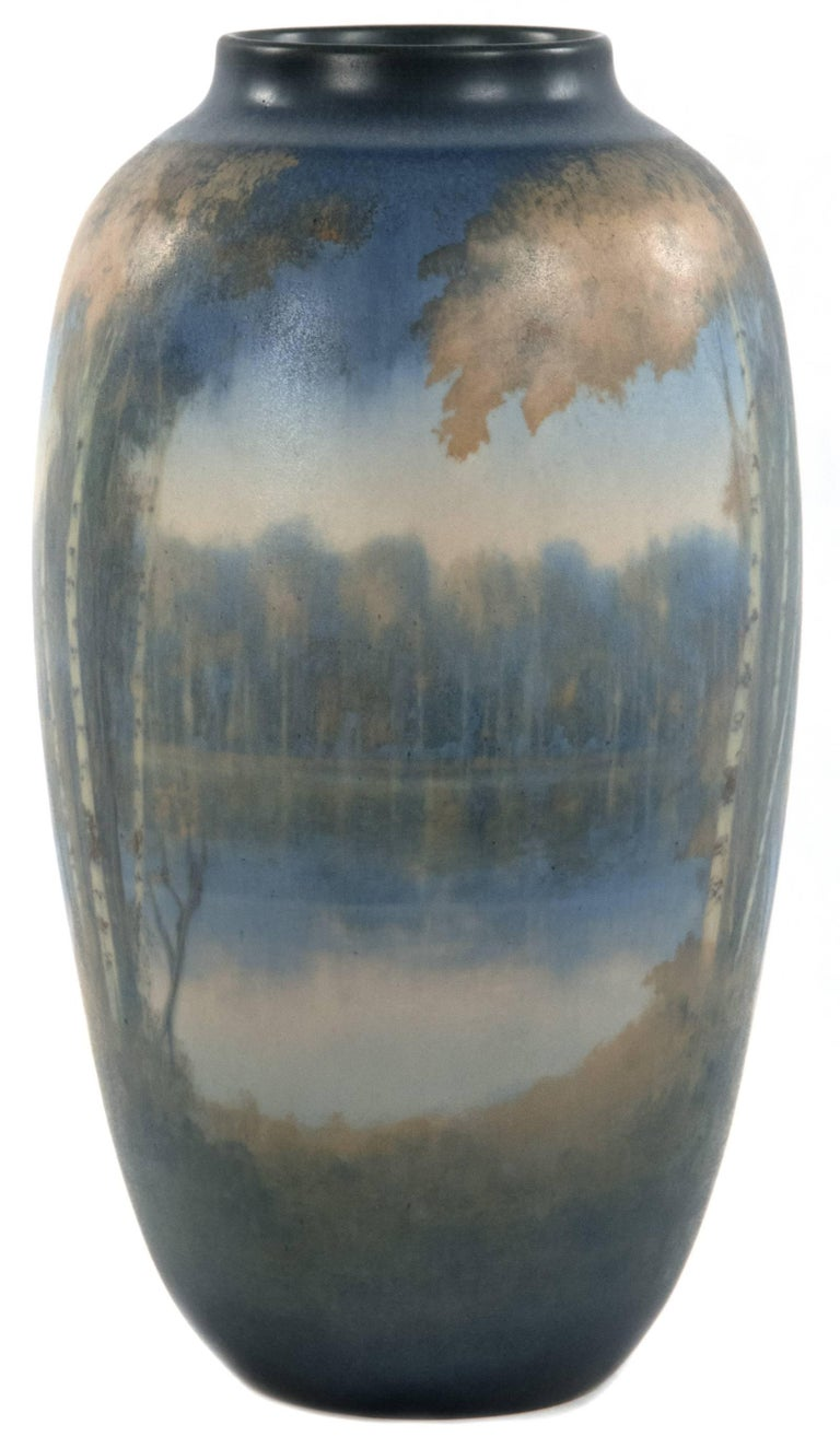 A tree-lined shoreline is reflected in a calm river in this atmospheric landscape that is softly illustrated in a neutral autumnal palette of blue, orange and brown glazes on this Rookwood Pottery vase of ovoid form dating from the mid-20th century.