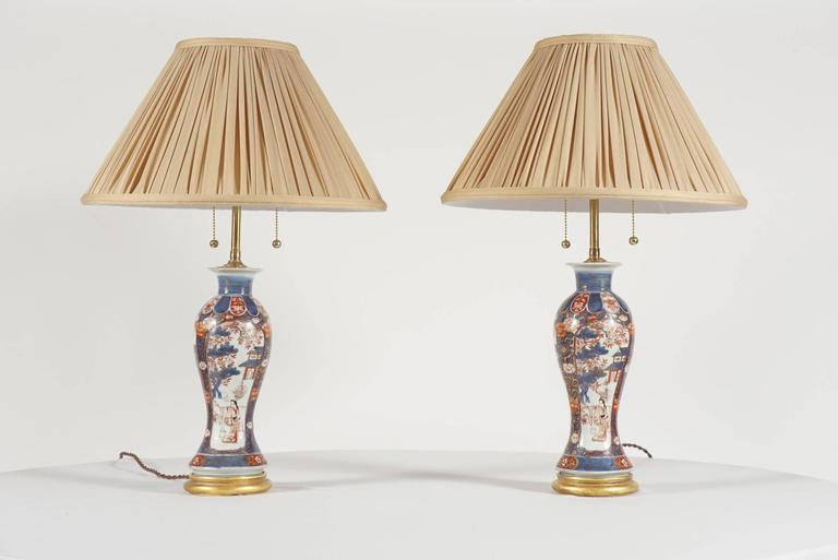 Elegant pair of Chinese export early Qing Dynasty garniture baluster vases, converted to lamps circa 1930, having the Imari palette of underglaze blue, iron red, and gilding with figural, foliate, and architectural motifs in panels, fitted to turned