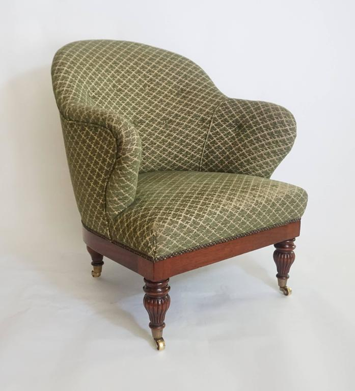 """George IV, William IV period English Regency tub or club chair having upholstered frame with """"barrel"""" back and """"butterfly"""" arms connecting to D-shaped seat on exposed solid mahogany base with circular turned and reeded tapering"""