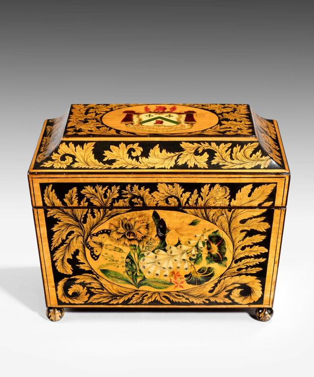 A superb Regency period penwork tea caddy of sarcophagus form; the tea caddy's lid decorated with a coat of arms and the sides with butterflies and flowers including lilies, foxgloves and roses surrounded by scrolling acanthus leaves; the tea