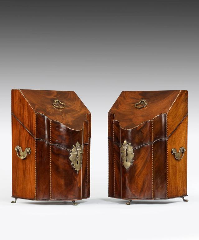 A pair of George III Sheraton period mahogany knife boxes; the knife box's lift-up lid is veneered in flame Cuban mahogany with barber's pole stringing and retains the original axe-head handle, the lid opens to reveal a fully fitted interior. The