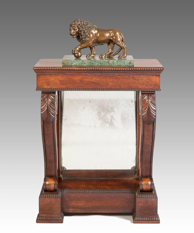 A Regency period rosewood console table; the table's well figured top with a gadrooned edge raised on scrolling legs which are boldly carved with acanthus leaves and terminate in a plinth base which is decorated with an unusual ripple moulding. The