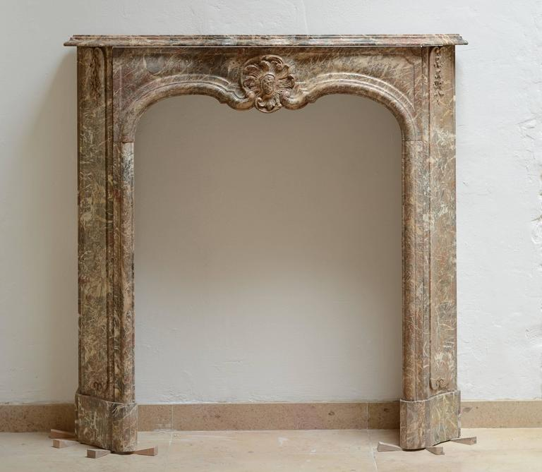 Stunning and unique little late 18th century Régence fireplace. The perfect apartment decoration! This mantelpiece is made from the finest Belgian rouge royal mable. The foliage on both jambe are little masterpieces as is the cartouche in the center