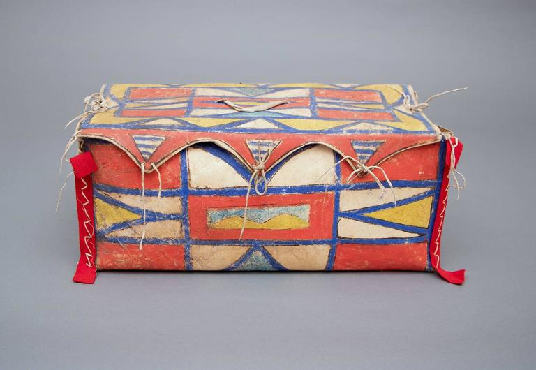 A rare box form constructed of rawhide and intricately painted in an abstract design with natural pigments and red trade cloth. This was created by a North American Indian living in the Plateau cultural area - encompassing portions of what is now