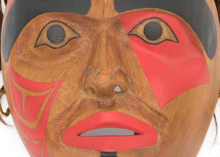 A carved wooden mask originating in the Pacific Northwest Coast. The design on the face is a Native American Killer Whale or Orca motif in black and red. The title, date and the artist's initials,