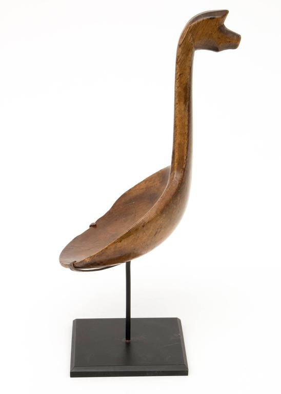 A carved wooden spoon with a horse effigy on the handle. Custom display stand is included. Measurements including the stand are 11 ¼ x 3 ¾ x 3 ¾ inches. Originating from a great lakes/woodlands tribe.