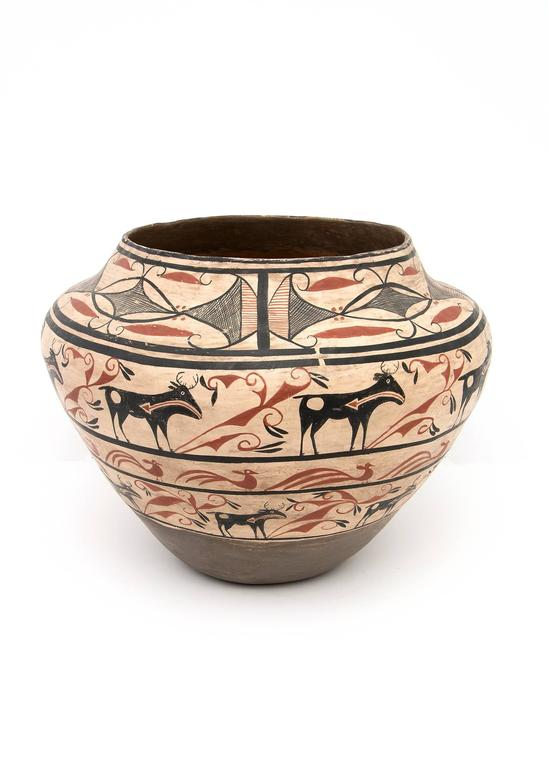 This large earthenware olla was built by hand and exquisitely painted in slip glazes in a Classic Zuni design including heartline deer in red and black against a ivory background.  Although this is very well crafted and consistent with 19th century
