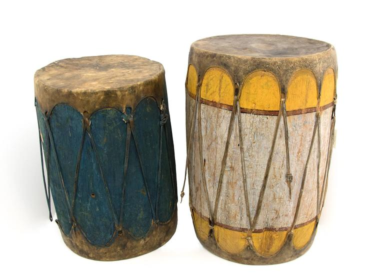 Two Pueblo drums from the early 20th century constructed of wood with stretched rawhide and vegetal paint. Dimensions as displayed: 28 x 38 inches. Individual measurements: Left (blue): 24 H x 18 Di inches. Right (yellow): 28 H x 17 Di inches. These