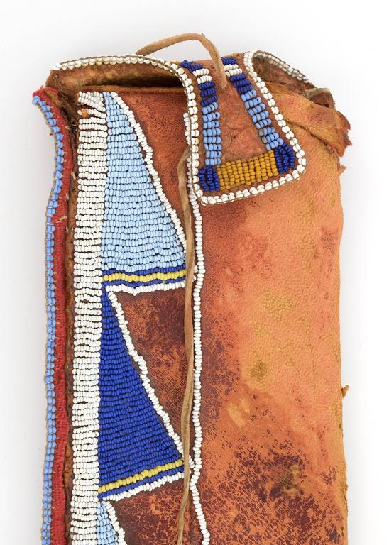A Classic Period (Pre-Reservation era) knife sheath.  Constructed of Native tanned hide and partially beaded with blue, white and yellow trade beads.  There is red trade cloth along the edge and the hide is rubbed in red ochre.  Twoi hide drops are