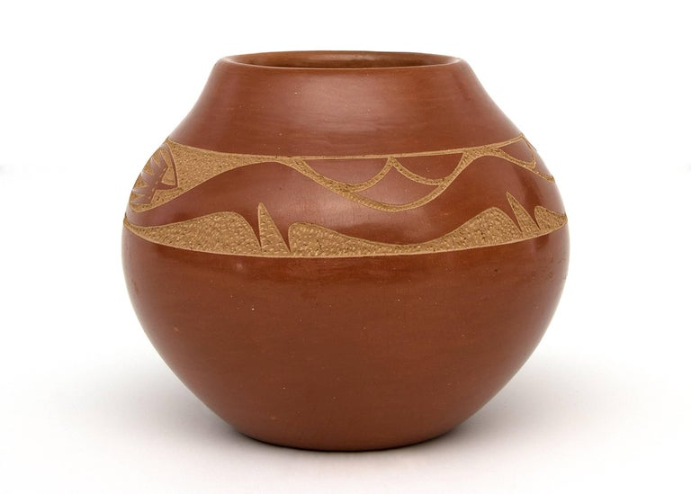 A redware olla with a sgraffito/incised Avanyu water serpent by San Ildefonso potter, Tony Da, Thun-Phoe-She (Sun Dew). Earthenware with slip glazes, signed on base by the artist.