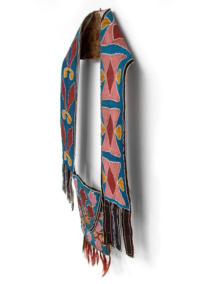 A Bandolier or Delaware bag dating to the Classic period (1650-1875) of Native American Indian art. Constructed circa 1850 of trade beads, red stroud cloth dyed with lac or cochineal, calico, red and blue ribbon (remnants) tin cone danglers w/ red