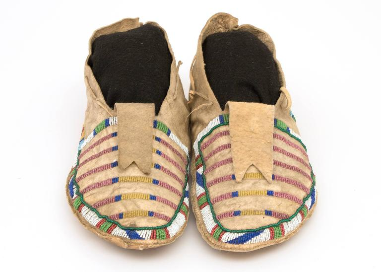 A vintage/antique pair of Native American beaded moccasins, created circa 1870 during the Late Classic Period of North American Indian art by a Crow (Plains Indian) artist. Composed of native tanned hide and partially beaded in a classic banded