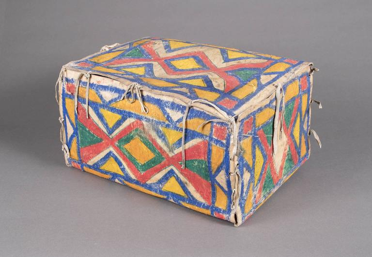 An antique Sioux (Plains Indian) parfleche container in a box form. Constructed of rawhide and painted with natural pigments (vegetal paints) in abstract geometric designs. A Nomadic tribe, the Sioux are associated with areas of the great plains of