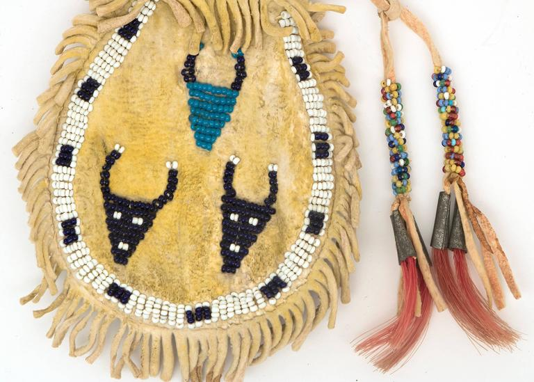 Transitional plains pouch from the last quarter of the 19th century. Constructed of native tanned hide and partially beaded with trade bead. Side 1: three buffalo pictographs; side 2: cross motif; with yellow ochre pigment on both sides and tin-cone