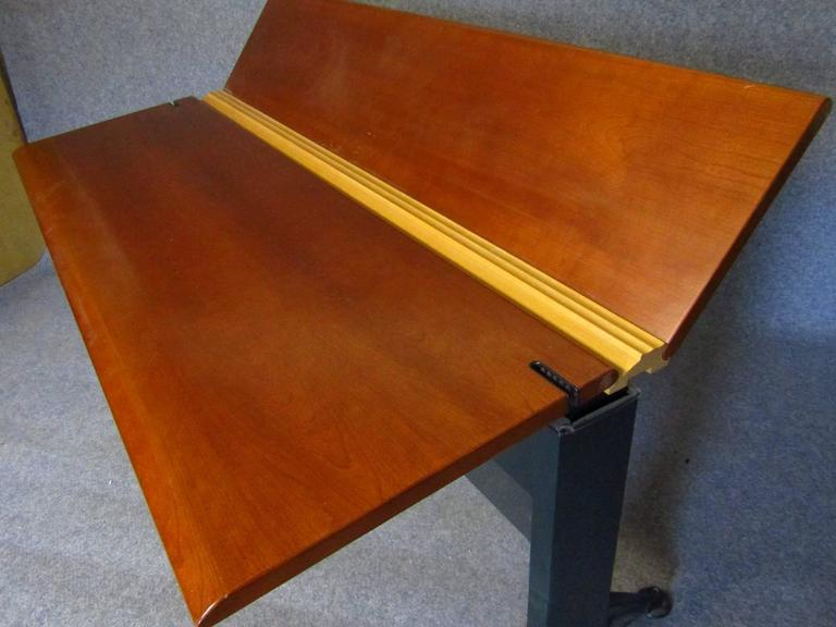Adjustable desk by Geoff Hollington for Herman Miller (signed).  This high performance adjustable desk can function as a stand up or seated work surface. The table desk has a back surface that tilts up for display or lays flat for an enlarged work
