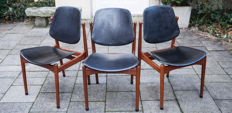 Arne Vodder Danish modern solid teak dining chairs made by France and Son of Denmark from 1957. Markers label with brass medallions and embossed insignia. The tilting black leather backs cradle the body for a very comfortable seating position.