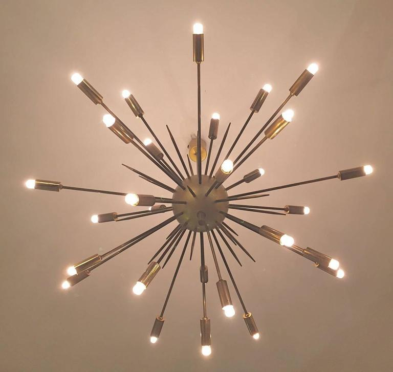 An original Italian Sputnik brass chandelier edited by Stilnovo in the 1950s.The lamp is composed of 24 arms attached to a brass ball and to a brass suspension stem. Excellent condition.