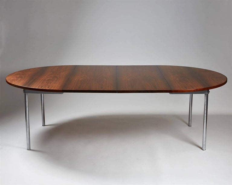Dining table designed by Hans Wegner for Andreas Tuck, Denmark, 1961. Rosewood and brushed steel.   Measures: H 70.5 cm / 27 3/4'' D 135 cm / 53 1/4'' Total length 235 cm / 7'9'' Two extension leaves at 50 cm / 19 3/4'' each.