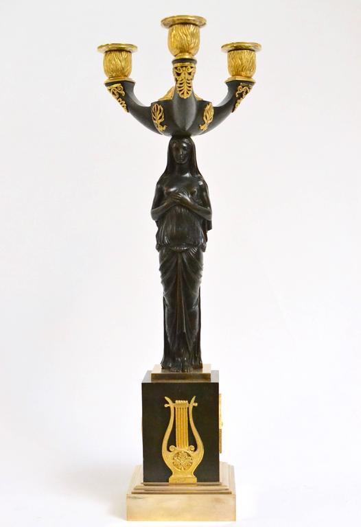 A pair of gilt and patinated bronze Empire candelabra, circa 1810-1820.