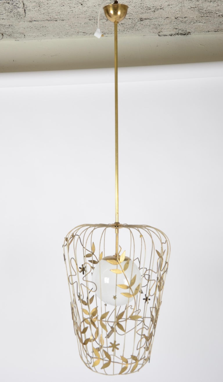 A large pendant designed by Hans Bergström for Ateljé Lyktan, Sweden, 1950s. Opal glass with enclosed brass cage decorated with brass flowers and leaves. Original label.