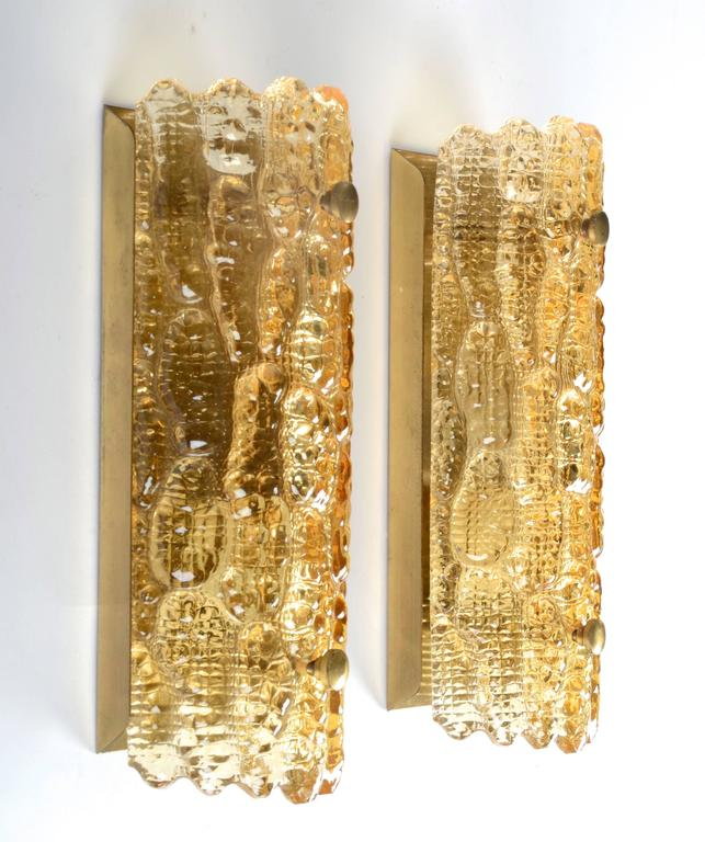 A pair of textured bent glass sconces with brass backplate, by designer Carl Fagerlund for Orrefors.
